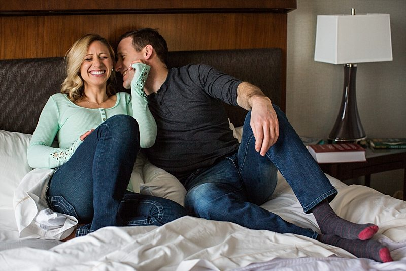 A lifestyle portrait of a couple sitting in bed and laughing together.