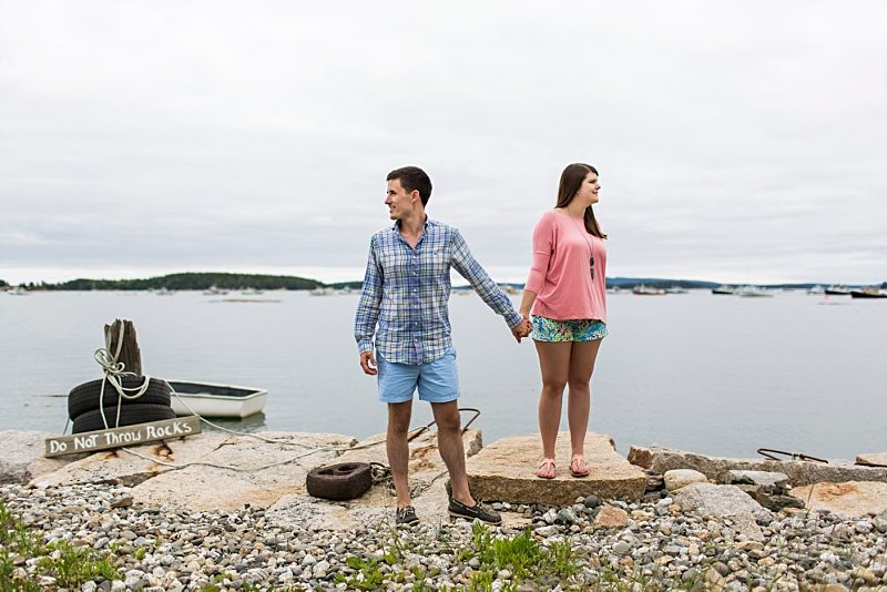 A couple holds hands at water's edge in Stonington, Maine.