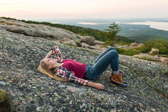A girl lies on Cadillac Mountain for her senior portraits.