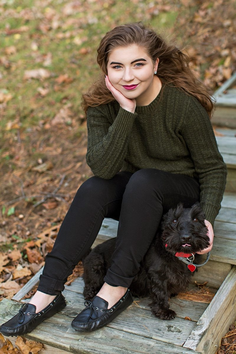 A senior poses with her Scottie dog.