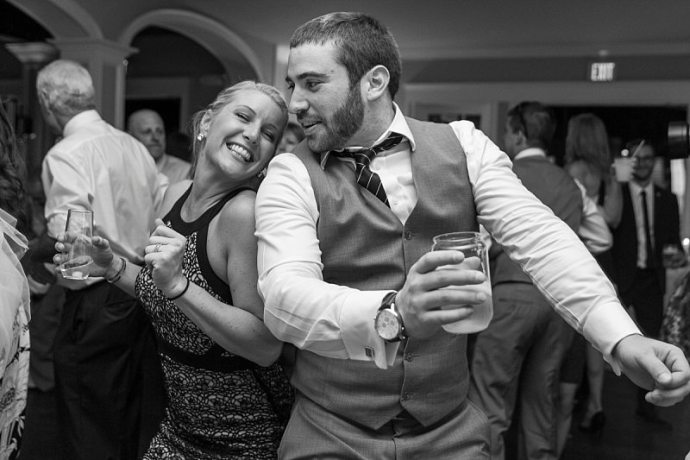 A photo of wedding guests happily dancing back-to-back at a wedding.