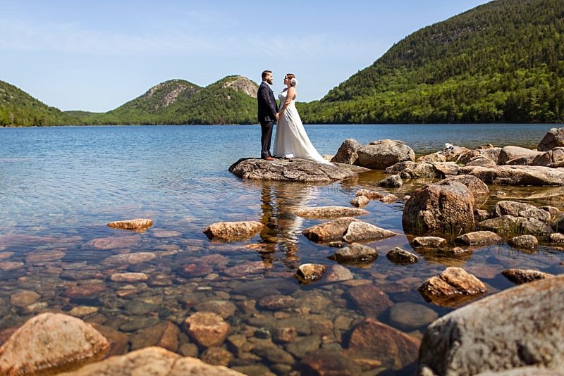 A portrait of a bride and groom on a sunny day at Jordan Pond in Acadia National Park. They stand on rocks jutting out into the water, holding hands.