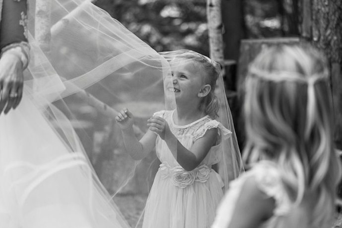 A black and white photo of a flower girl playing in the bride's veil.