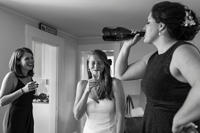 A bride and her bridesmaids laugh as they finish a bottle of champagne before the wedding ceremony.