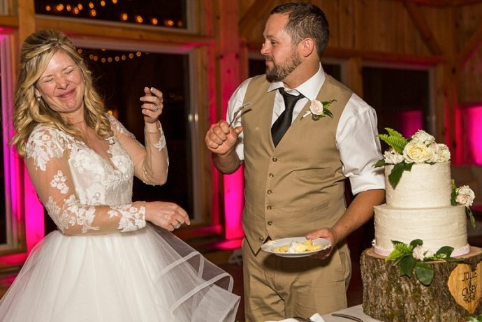 A bride wrinkles her nose and laughs as the groom tries to smear cake on her face.