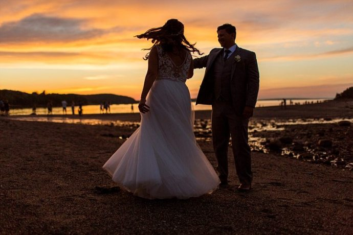 A silhouette of a groom twirling a bride at sunset.