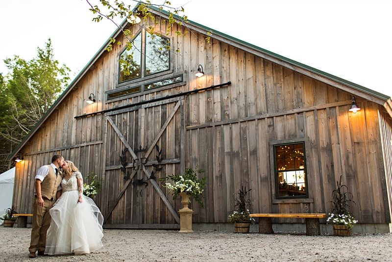 A bride and groom kiss in front of the barn at Granite Ridge Estate & Barn in Norway, Maine.