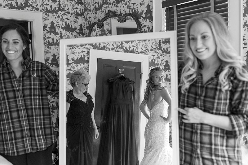 Two bridesmaids hold a mirror as the bride and her mother admire her in her wedding gown.