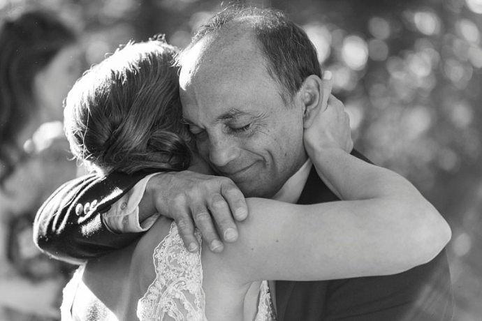The father of the bride tears up as his daughter hugs him.