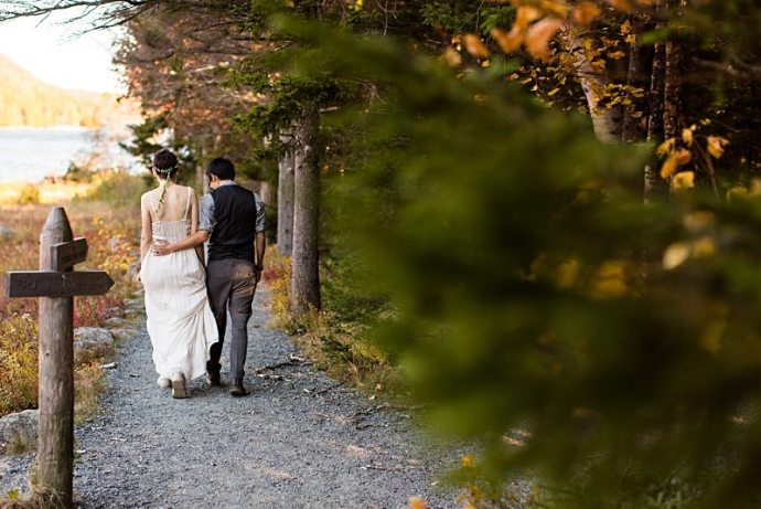 The groom puts his arm around the bride as they walk along the trail at Jordan Pond in Acadia National Park.