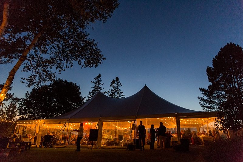 A wedding tent lit up at twilight.
