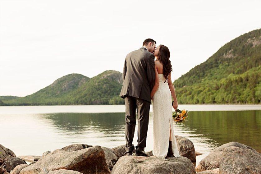 Bride and groom kiss at Jordan Pond.