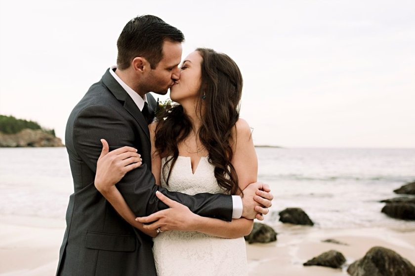Bride and groom kiss at Sand Beach in Acadia National Park.