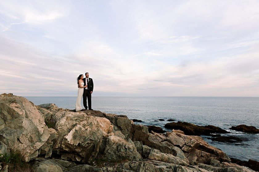 Bride and groom stand on cliffs at Otter Point in Acadia National Park at sunset.