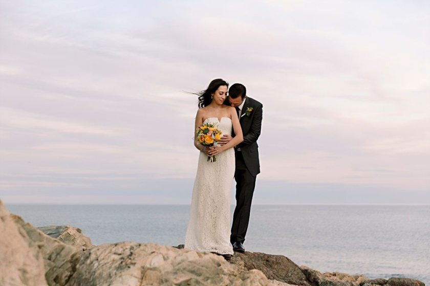 Bride and groom pose on cliffs at Otter Point in Acadia National Park.