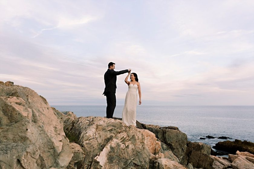 Bride and groom dance on cliffs at Otter Point in Acadia National Park.