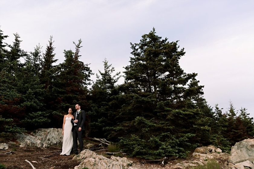 Bride and groom stand together at Otter Point.