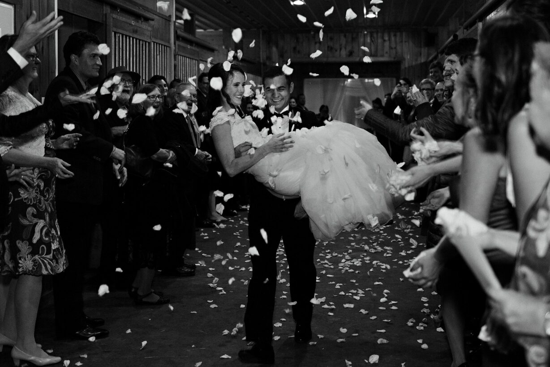 Groom carries bride through petal toss