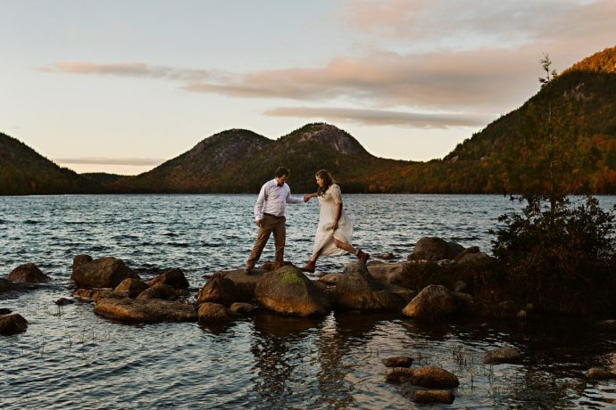 Newlyweds walking on rocks at Jordan Pond in Acadia National Park