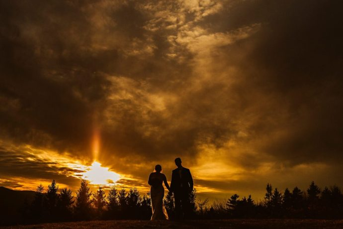 Silhouette of bride and groom walking at sunset