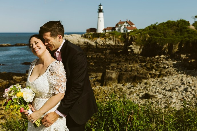 Couple pose in front of Portland Head Light at Portland Maine elopement