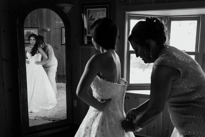 Bride getting zipped into wedding dress