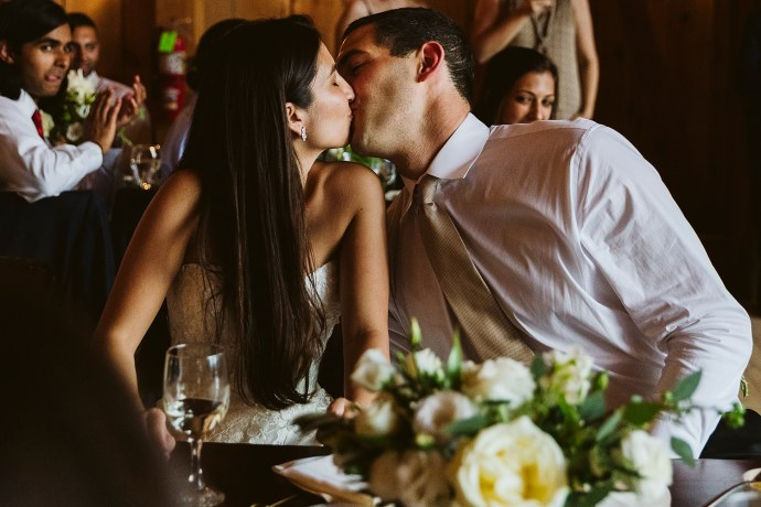 bride and groom kiss at wedding reception