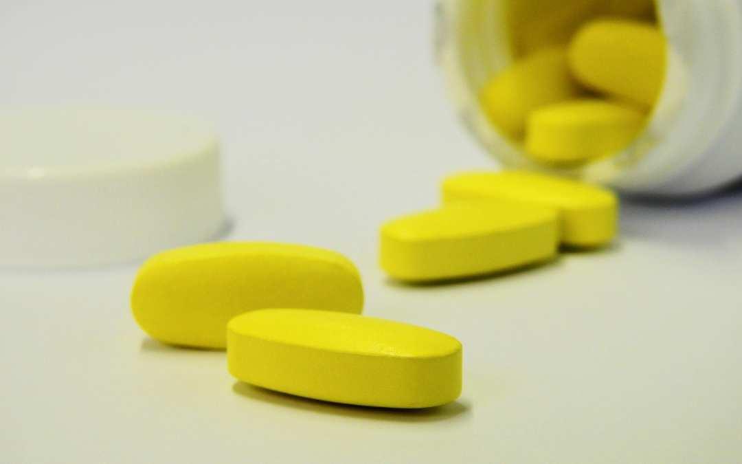 bottle of yellow vitamin pills