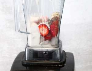 blender on white counter top with strawberries, chia seeds and ice