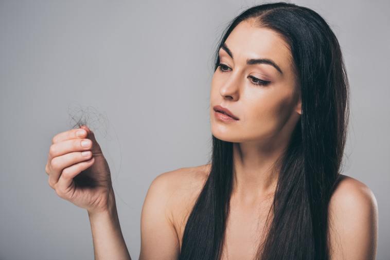 young  woman holding fallen hair; hair loss