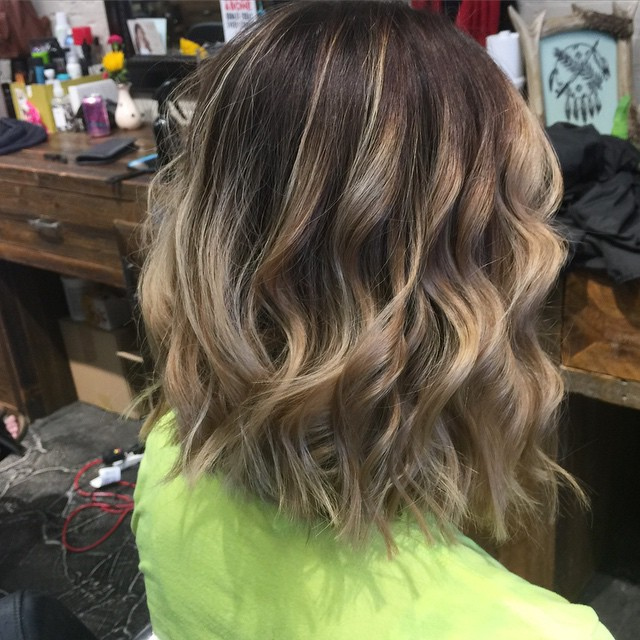 back view of medium messy bob hairstyle with highlights