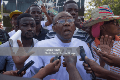 Father Amos George, the head of the political party ethics Pitit Dessalines talks to reporters before participating in a demonstration in Port-Au-Prince, December 5, 2017.Several civil society organizations took part in a march against corruption Tuesday, December 5, 2017. The initiative was taken by the Collective December 4, a human rights organization.