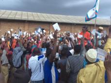 Wanachama wapya wakionesha kadi zao kwa waandishi wa habari na wananchi waliohudhuria.