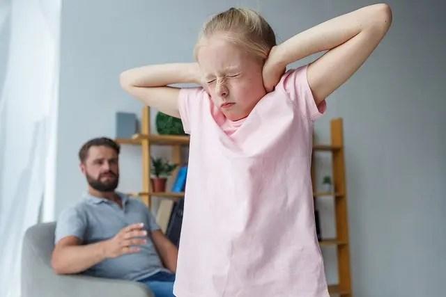 パパに怒られ耳をふさぐ女の子の写真