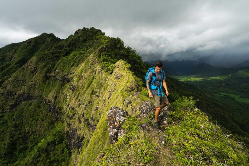 Hiker atop green mountaintop in Hawai'i