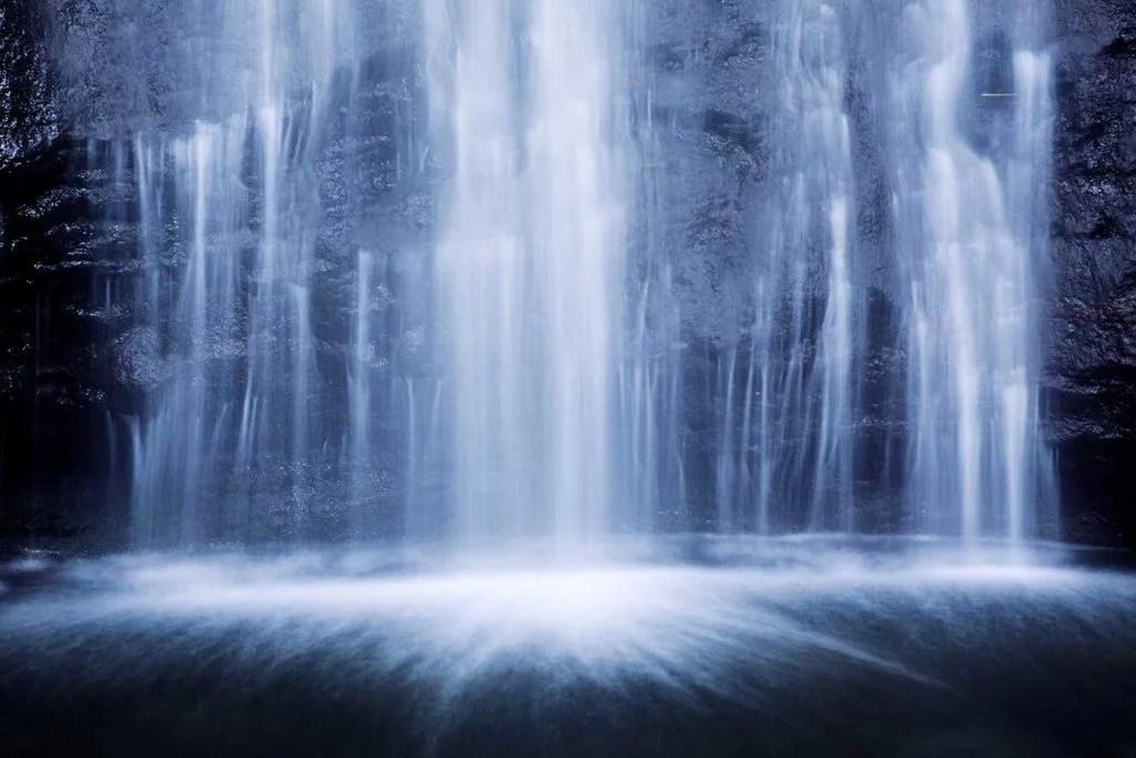 waterfalls spilling over dark rocks