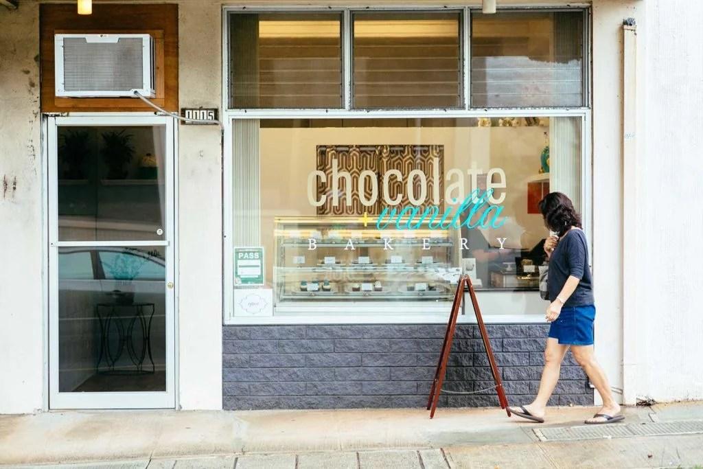 woman walking on sidewalk in front of Chocolate + Vanilla Bakery