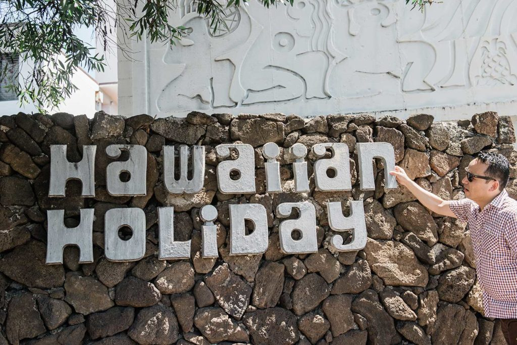Chae Ho Lee in front of Hawaiian Holiday sign on rock wall