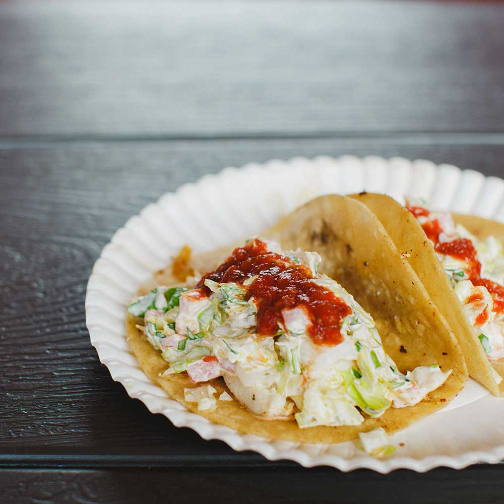 fish taco with salsa on white paper plate