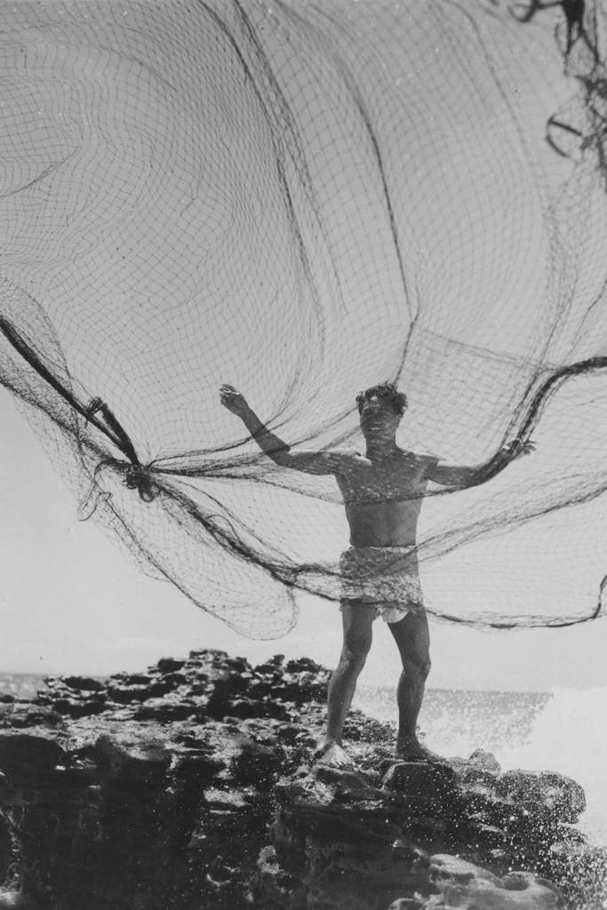 black and white photo of man casting fishing net