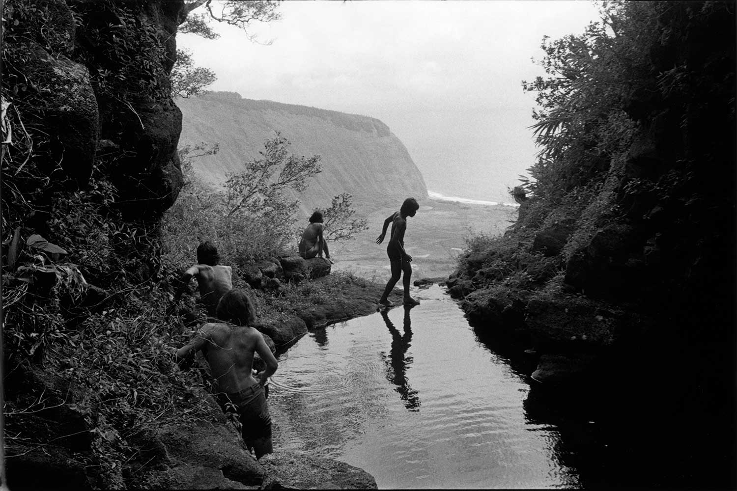 Black and white photograph of youths hiking above Hi'ilawe Falls in Waipi'o Valley