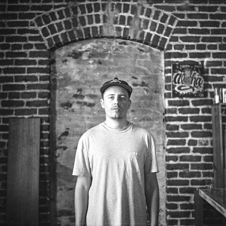 black and white photo of Filmmaker Filipe Zapelini in front of brick wall