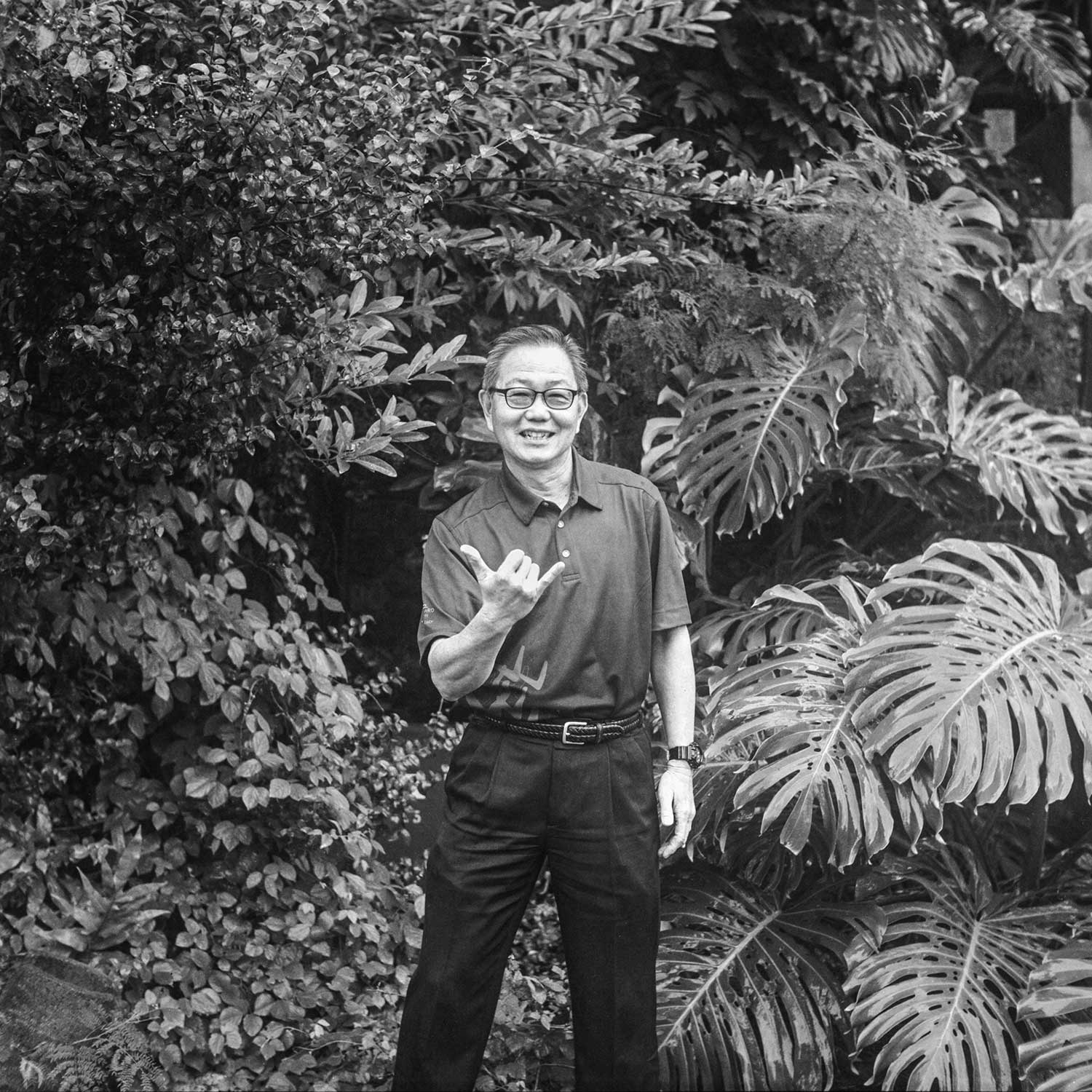 black and white photo of Robin Kimura giving the shaka in front of forest