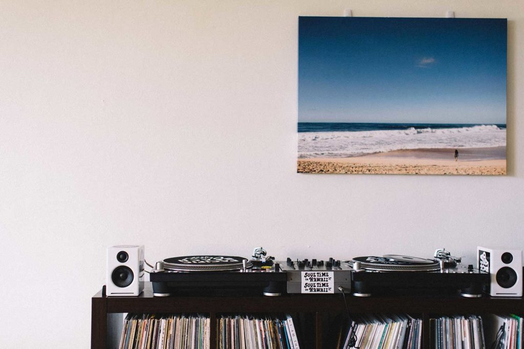 records and turntables with ocean painting on wall