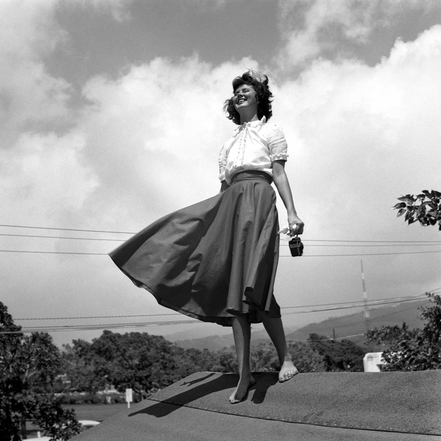 Black and White photo of woman standing on roof, wind blowing her skirt