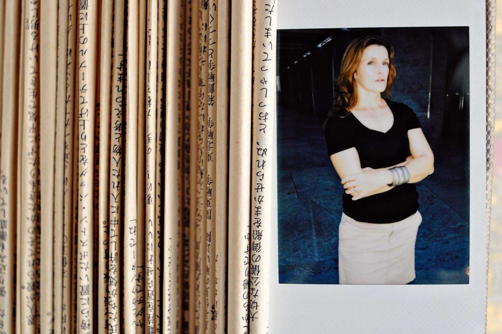 photo of Jacqueline Rush Lee with pages from books
