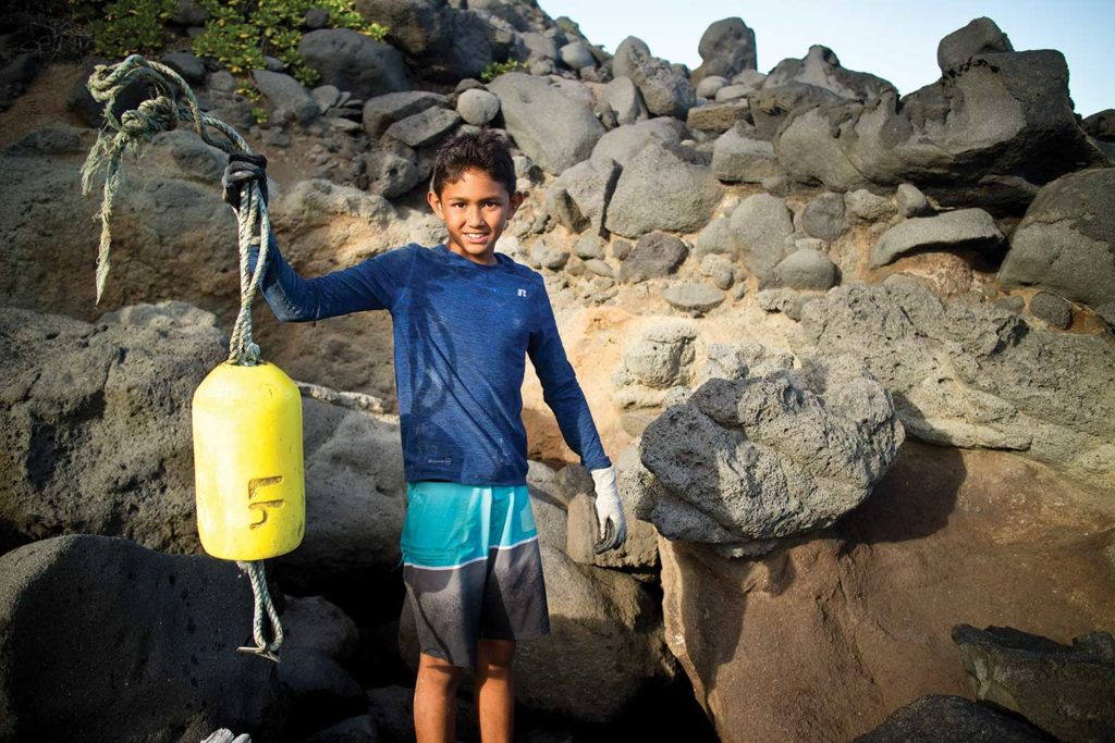 Young boy cleaning littered plastic from beach rocks