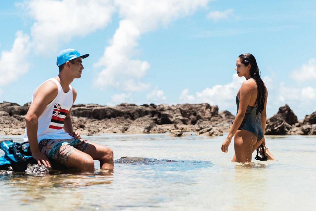 man and woman in swimsuits in shallow ocean water