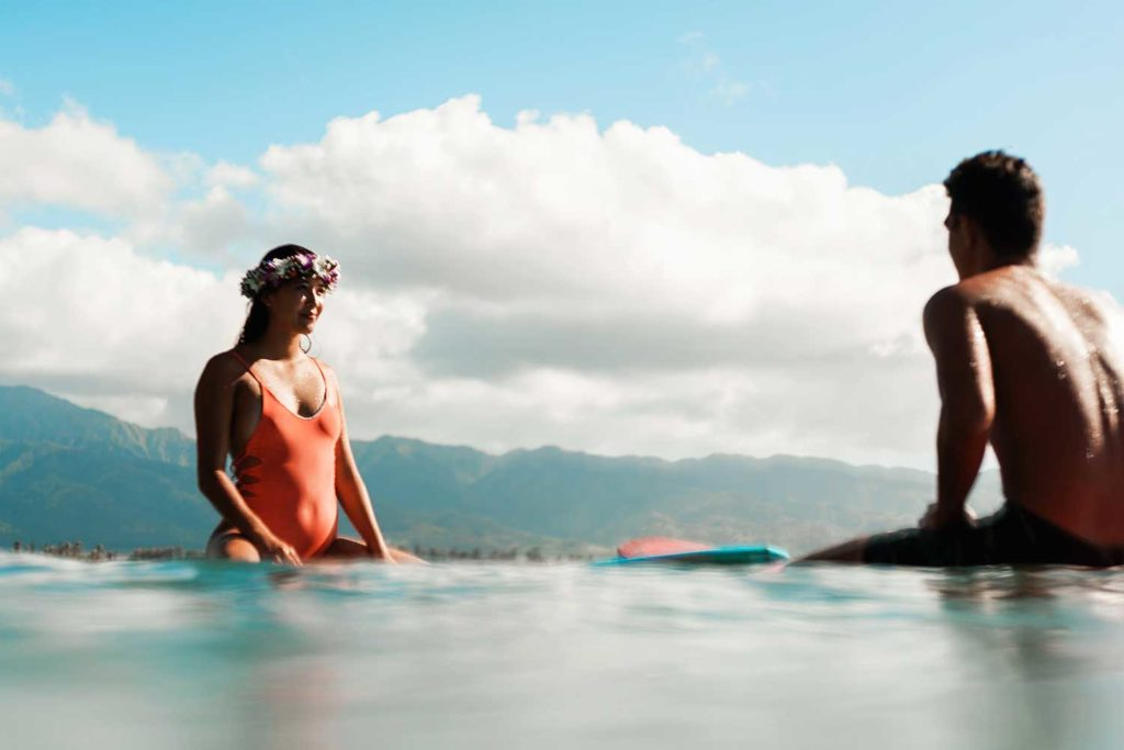 Woman and man sitting on surfboards in the ocean