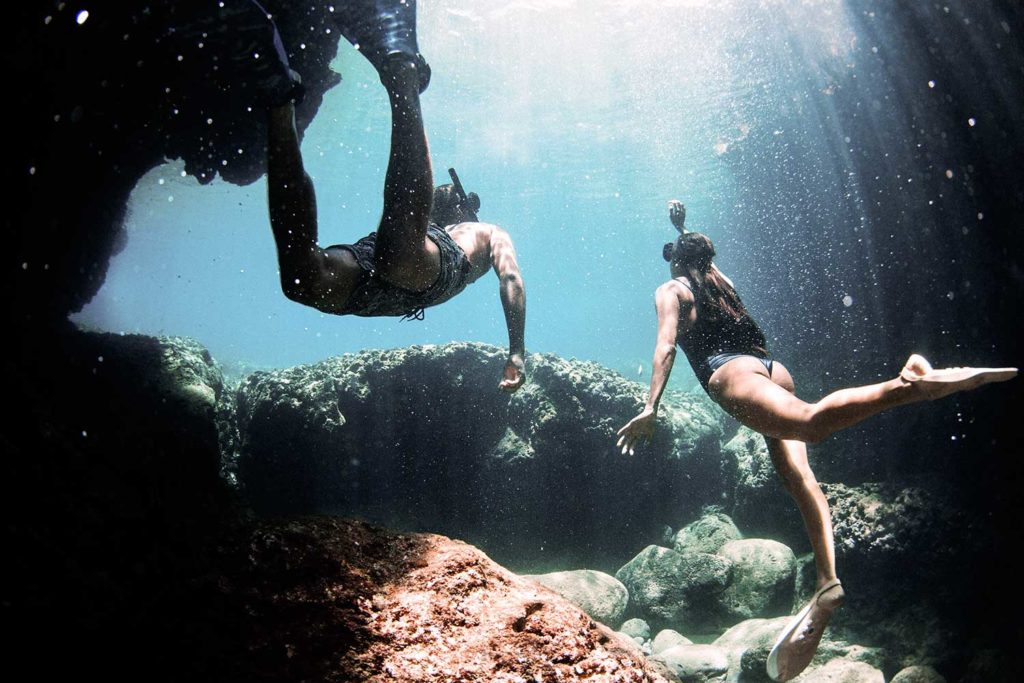 Man and woman snorkeling underwater near coral rocks
